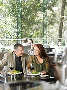 Couple smiling over wine at outdoor bar