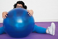 Uninspired overweight Woman sitting Behind Exercise Ball (thumbnail)