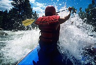Kayaker paddling through Rapids back view