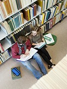 Students sitting on floor doing homework in library (thumbnail)