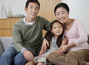 Young couple and daughter Posing on Sofa (thumbnail)