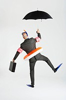 Middle_aged businessman in flippers inflatable rubber ring snorkel and goggles waddling carrying briefcase and umbrella back view