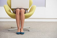 Casually dressed Businesswoman sitting in modern chair Using Laptop low section (thumbnail)