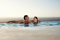 Couple relaxing in infinity pool at sunset