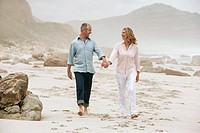 Couple walking on beach holding hands