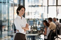 Businesswoman standing in office with group of office workers in background