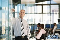 Businessman leaning on door in office with office workers in background