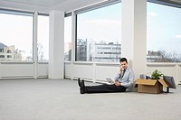 Office worker talking on phone sitting on floor of empty office space
