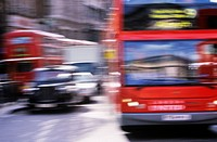 Red buses and black cabs on road in London motion blur