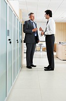Two businessmen talking in office corridor