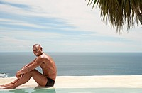 Man sitting at edge of pool ocean in background