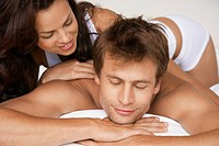 Woman massaging man lying in bed