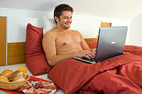 man with laptop has breakfast in bed