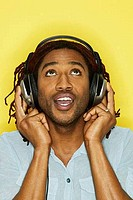 Close_up of a young man wearing headphones and singing