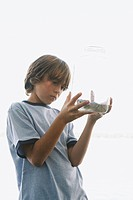 Boy examining frog in jar