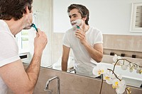 Man shaving at bathroom mirror