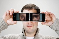 Young man using camera phones as eyeglasses