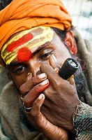An Indian Sadhu smokes ganja from his chillum