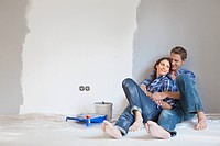 Couple hugging on floor of partially painted room