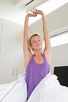 Woman stretching her arms on the bed at morning