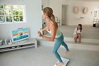 Woman doing step aerobics and watching TV