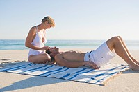 Man lying on woman's lap on the beach