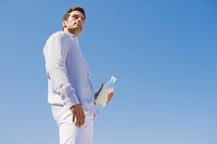 Man holding milk bottle on the beach
