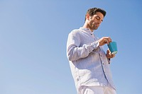 Man holding a cup of coffee on the beach