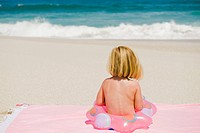 Girl sitting with an inflatable ring on the beach (thumbnail)