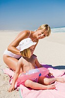 Woman applying suntan lotion on her daughter on the beach (thumbnail)