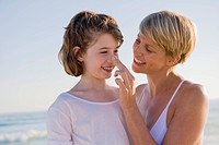 Woman with her daughter enjoying vacations on the beach