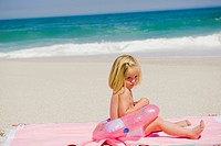 Girl sitting with an inflatable ring on the beach