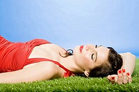 Young woman lying on artificial grass (thumbnail)