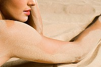 Woman with sand on her skin