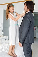 Girl adjusting groom's tie