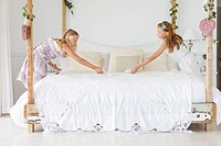 Two girls decorating a bed (thumbnail)