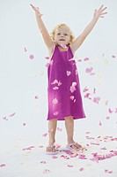Girl tossing flower petals and smiling