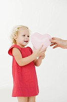 Girl taking a heart shape balloon