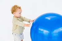 Baby boy playing with a fitness ball