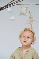 Close_up of a baby boy with toys hanging from sticks above him