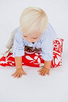 Baby boy crawling on a cushion