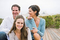 Woman sitting on a boardwalk with her parents