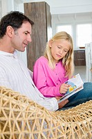 Man and his daughter reading a book