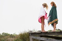 Two girls standing on a boardwalk