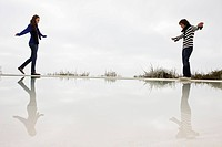 Couple walking on the ledge of a swimming pool
