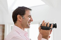 Man holding a home video camera and smiling