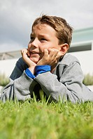 Boy lying on grass and day dreaming