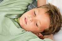 Close_up of a boy lying on the bed