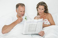 Couple reading newspaper on the bed