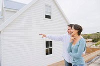 Man pointing towards a house with a woman standing beside her